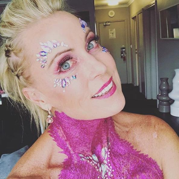 A photo of Lisa Curry covered in pink body glitter on set of The All New Monty: Ladies' Night.