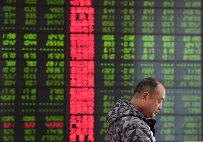 A man is seen against an electronic board showing stock information at a brokerage house in Fuyang, Anhui province, China March 23, 2018. China Daily via REUTERS