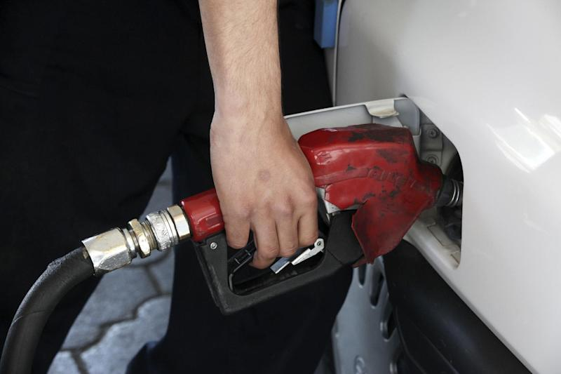 A gas station worker fills a car in central Tehran, Iran, Friday, April 25, 2014. The Iranian government on Friday cut a portion of fuel subsidies, nearly doubling some prices at the pump as part of a second round of cuts delayed since 2012. (AP Photo/Vahid Salemi)