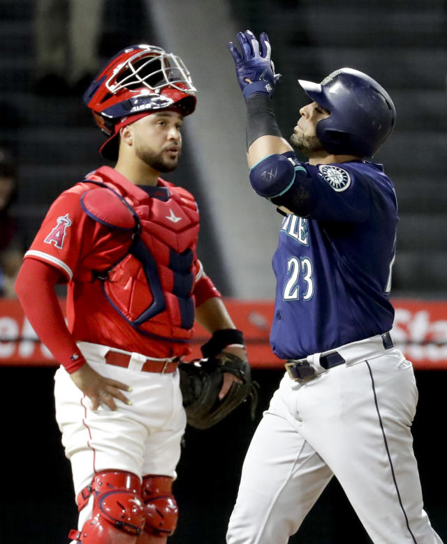 Seattle Mariners' Nelson Cruz, right, celebrates after his three-run home run past Los Angeles Angels catcher Francisco Arcia during the fourth inning of a baseball game against the Los Angeles Angels in Anaheim, Calif., Thursday, Sept. 13, 2018. (AP Photo/Chris Carlson)