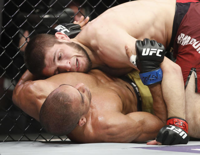 Khabib Nurmagomedov, top, fights Edson Barboza in a lightweight mixed martial arts bout at UFC 219, Saturday, Dec. 30, 2017, in Las Vegas. (AP Photo/John Locher)