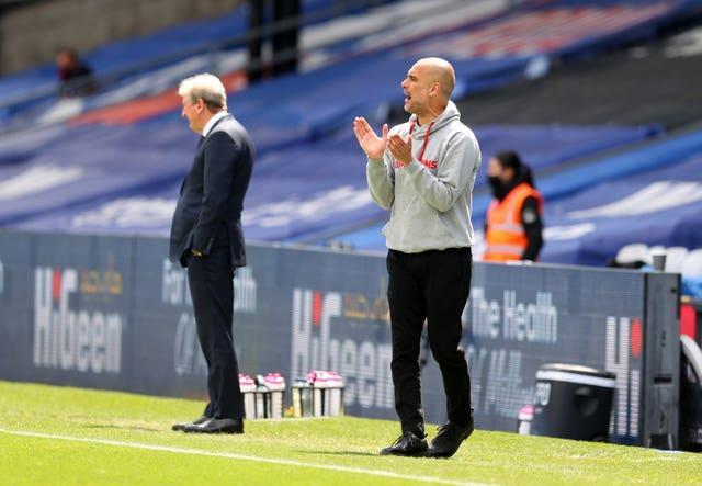 Manchester City manager Pep Guardiola, right, watches on