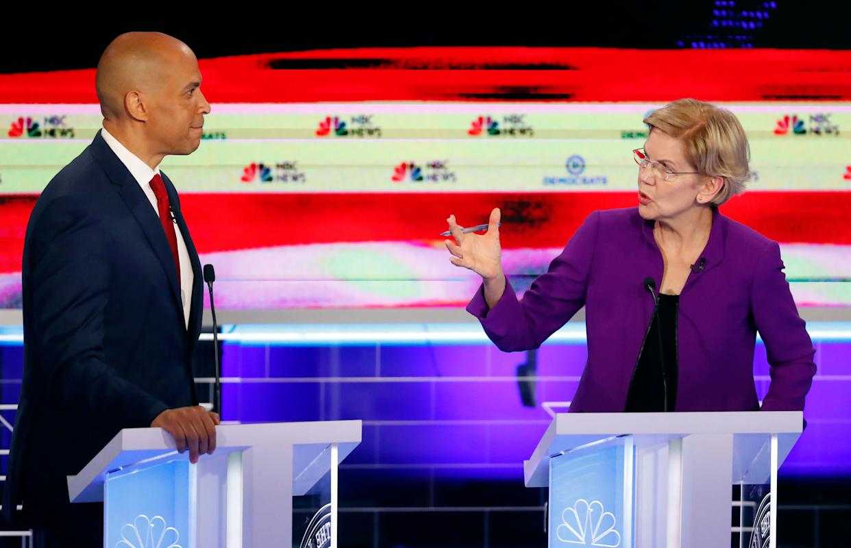 Sen. Elizabeth Warren (D-Mass.) talks with Sen. Cory Booker (D-N.J.) during the first Democratic primary debate. The 2020 presidential candidates largely stuck to their progressive stances. (Photo: Wilfredo Lee/ASSOCIATED PRESS)