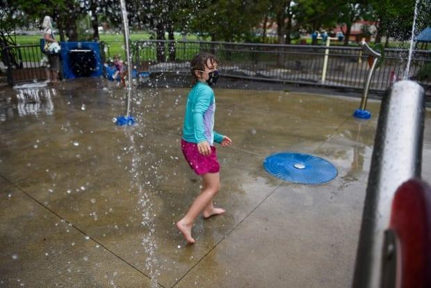 Seven-year-old Lexie F. wears a mask while playing at a splash pad in Ottawa on Friday, May 21, 2021, during the COVID-19 pandemic.