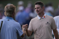 Justin Rose, of England, bumps fists with Will Zalatoris, left, on the 18th hole during the third round of the Masters golf tournament on Saturday, April 10, 2021, in Augusta, Ga. (AP Photo/Gregory Bull)