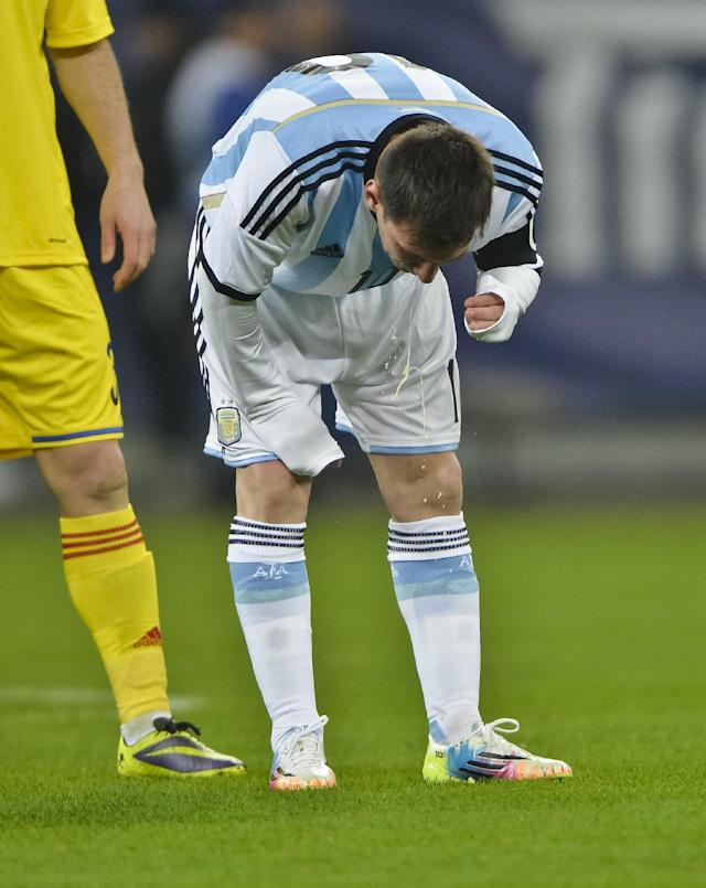 Argentina's Lionel Messi appears to vomit during an international friendly soccer game against Romania on the National Arena stadium in Bucharest, Romania, Wednesday, March 5, 2014. (AP Photo)