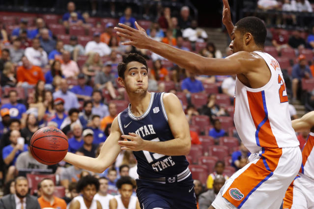 Utah State guard Abel Porter (15) passes past Florida forward Kerry Blackshear Jr. in the first half of an NCAA college basketball game, part of the Orange Bowl Classic tournament, Saturday, Dec. 21, 2019, in Sunrise, Fla. (AP Photo/Wilfredo Lee)