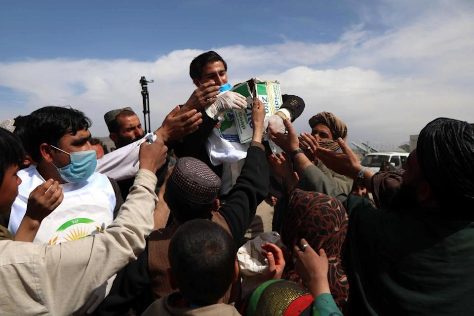 People gather to collect masks, gloves and disinfectants distributed to the public, in Herat, Afghanistan, 15 March 2020.