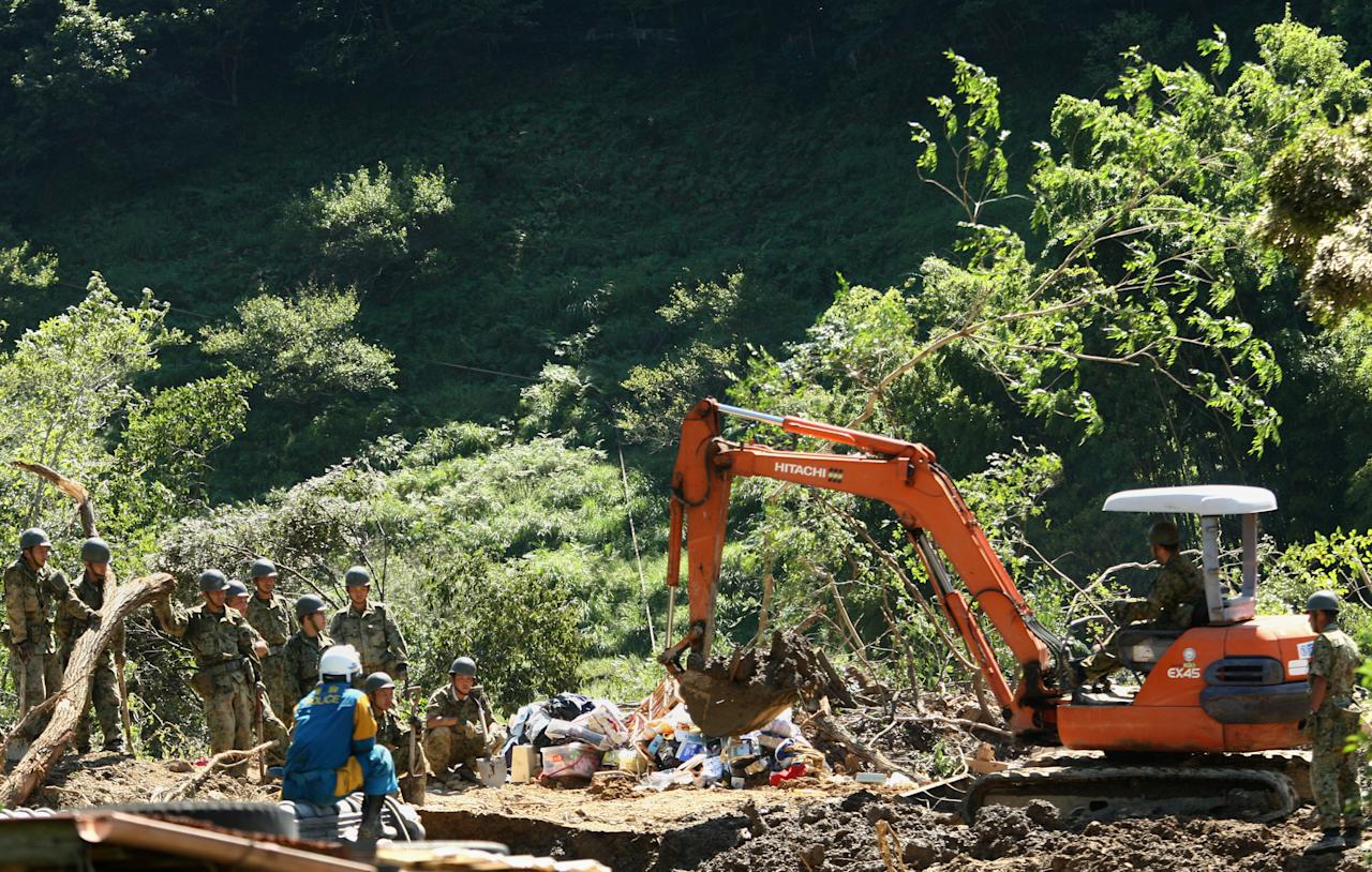 TANABE, JAPAN - SEPTEMBER 06:  Members of Ground Self-Defense Force, firefighters and police officers continue the search for missing people among the debris of houses destroyed by a landslide caused by heavy rain delivered by Typhoon Talas on September 6, 2011 in Tanabe, Wakayama, Japan. Rescue teams and aid are being brought into the area in the aftermath of the tropical storm which hit western Japan over the weekend, leaving 42 people confirmed dead and over 50 people still missing.  (Photo by Buddhika Weerasinghe/Getty Images)