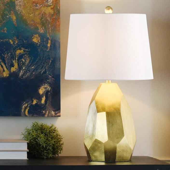 """This lamp has been hand-painted gold, giving it a distressed look that'll be cool on any desk. It is LED-compatible and has a polarized plug and a three-way switch. The lamp doesn't come with a bulb, so you'll have to get an <a href=""""https://amzn.to/3kiHd0q"""" rel=""""nofollow noopener"""" target=""""_blank"""" data-ylk=""""slk:E26 bulb"""" class=""""link rapid-noclick-resp"""">E26 bulb</a>. <a href=""""https://fave.co/3molNke"""" rel=""""nofollow noopener"""" target=""""_blank"""" data-ylk=""""slk:Find it for $77 at Wayfair"""" class=""""link rapid-noclick-resp"""">Find it for $77 at Wayfair</a>."""