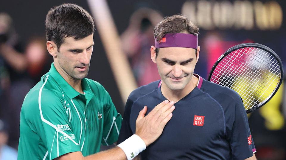 TOPSHOT - Serbia's Novak Djokovic (L) pats Switzerland's Roger Federer after his victory during their men's singles semi-final match on day eleven of the Australian Open tennis tournament in Melbourne on January 30, 2020. (Photo by DAVID GRAY / AFP) / IMAGE RESTRICTED TO EDITORIAL USE - STRICTLY NO COMMERCIAL USE (Photo by DAVID GRAY/AFP via Getty Images)