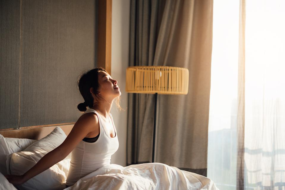 Beautiful young Asian woman with closed eyes stretching arms while waking up in bed in the morning.