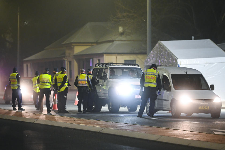 NSW Police officers speak to drivers crossing from Victoria into New South Wales (NSW) at a border check point in Albury. Source: AAP
