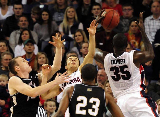 Gonzaga's Kevin Pangos, top center, gets caught rebounding with teammate Sam Dower (35) and Bryant's Joe O'Shea, left, and Alex Francis (23) in the first half of an NCAA college basketball game on Saturday, Nov. 9, 2013, in Spokane, Wash. (AP Photo/Jed Conklin)