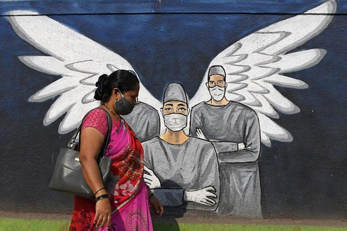 A woman wearing a face mask passes by a graffiti drawn to raise awareness about coronavirus disease. Graffiti is drawn not only to raise awareness of the coronavirus pandemic, but also to beautify the walls of Vasi (a suburb of Navi Mumbai).