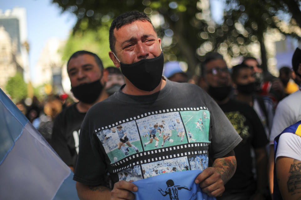 A man cries as he waits in a line outside the presidential palace to pay his final respects to Diego Maradona, in Buenos Aires, Argentina, Thursday, Nov. 26, 2020. The Argentine soccer great who was among the best players ever and who led his country to the 1986 World Cup title died from a heart attack at his home Wednesday, at the age of 60. (AP Photo/Rodrigo Abd)