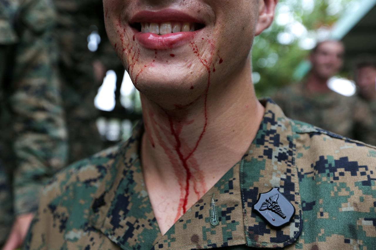"""A U.S. Marine smiles as blood from a cobra drips from his mouth during a jungle survival exercise as part of the """"Cobra Gold 2018"""" (CG18) joint military exercise, at a military base in Chonburi province, Thailand, February 19, 2018. REUTERS/Athit Perawongmetha     TPX IMAGES OF THE DAY"""