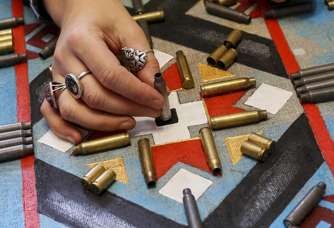 Ukrainian artist Dariya Marchenko works in her studio at pictures consisting of cartridges brought from the frontline in eastern Ukraine, in Kiev, July 22, 2015. Daria Marchenko calls her art approach philosophic symbolism where every element has its hidden meaning. In her works cartridges mean human's life that was brutally ended. Picture taken July 22, 2015. REUTERS/Gleb Garanich