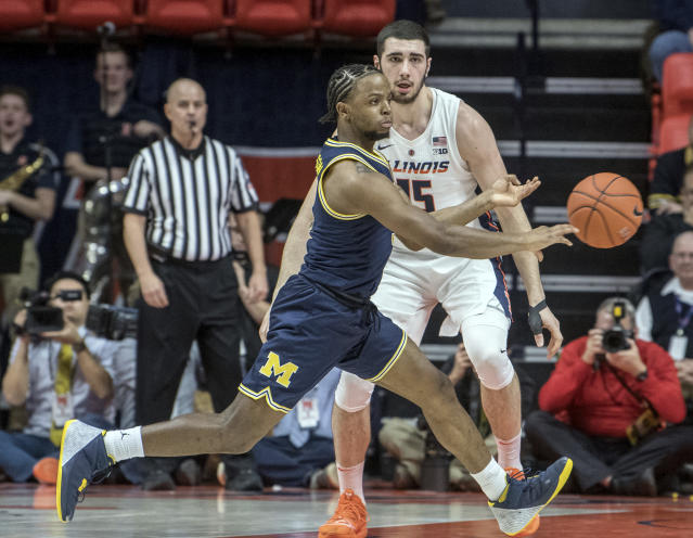 Michigan guard Zavier Simpson passes the ball as Illinois forward Giorgi Bezhanishvili (15) defends during the first half of an NCAA college basketball game in Champaign, Ill., Thursday, Jan. 10, 2019. (AP Photo/Rick Danzl)