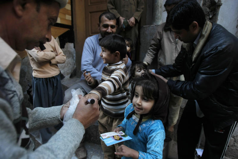 "In this Feb. 9, 2014 photo, Pakistani health workers vaccinate children against polio, in Peshawar, Pakistan. Pakistan's beleaguered battle to eradicate polio is threatening a global, multi- billion dollar campaign to wipe out the disease worldwide. Because of Pakistan, the virus is spreading to countries that were previously polio free, say U.N. officials. ""The largest poliovirus reservoir of the world,"" is in Peshawar, the capital of Pakistan's northwest Khyber Pukhtunkhwa province, which borders Afghanistan, according to the World Health Organization. (AP Photo/Mohammad Sajjad)"