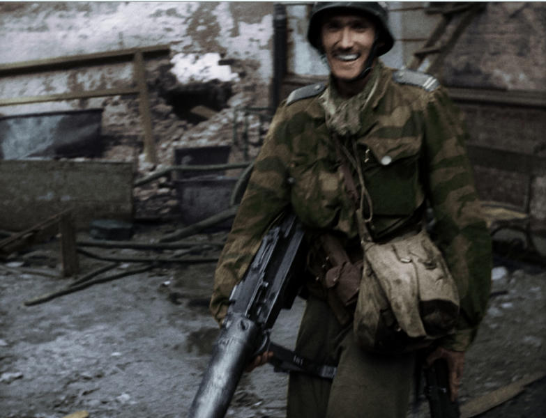 This is frame grab made available by the Warsaw Rising Museum shows Witold Kiesun taken from snippets of historical footage from the 1944 Warsaw Uprising, enhanced by modern coloring and sound techniques . The scenes are as riveting as any Hollywood war movie. But they are snippets of historical footage from the 1944 Warsaw Uprising, enhanced by modern coloring and sound techniques _ and turned into a movie. Kiesun is a smiling fighter filmed in a trophy German helmet and uniform, toting a captured machine gun and ammunition: Witold Kiezun, now 91, remains active in Warsaw as a professor of economics and management. (AP Photo/Warsaw Rising Museum)