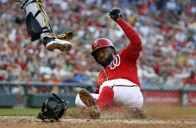 Washington Nationals' Denard Span slides safely into home as Pittsburgh Pirates catcher Russell Martin jumps to field the throw during the seventh inning of a baseball game at Nationals Park, Sunday, Aug. 17, 2014, in Washington. (AP Photo/Alex Brandon)