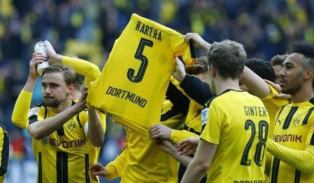 Borussia Dortmund players display a Marc Bartra shirt as they celebrate after the match