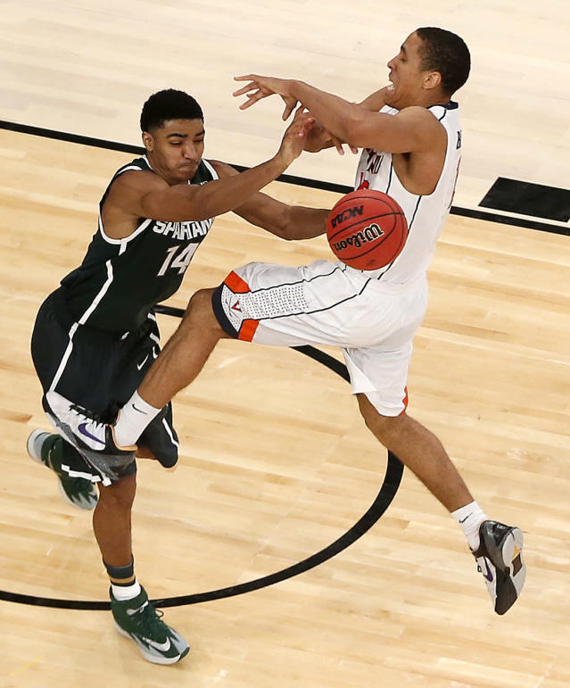 Virginia guard Malcolm Brogdon, right, is fouled by Michigan State guard Gary Harris during second half in a regional semifinal at the NCAA men's college basketball tournament, Friday, March 28, 2014, in New York. (AP Photo/Julio Cortez)