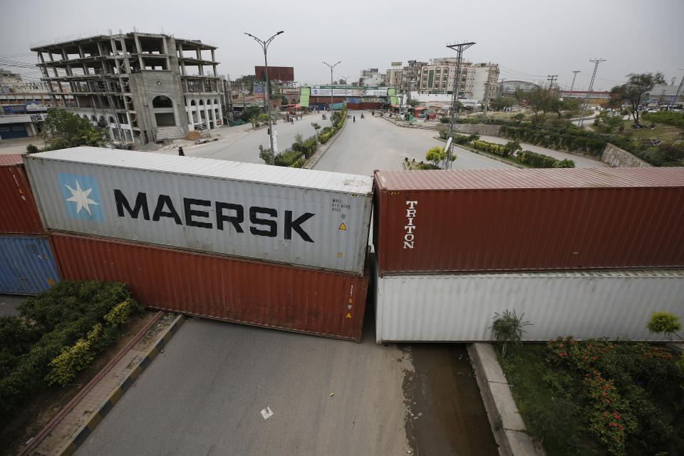 Authorities place shipping containers to block a road leading to the capital as a security measure on the possible anti-France protest march by a banned radical Islamists Tehreek-e-Labaik Pakistan party, in Rawalpindi, Pakistan, Tuesday, April 20, 2021. Pakistan's Parliament is expected to consider a resolution on Tuesday about whether the French envoy should be expelled over the publication of controversial cartoons depicting Islam's Prophet, testing whether the government gives in to threats from radical Islamists. (AP Photo/Anjum Naveed)
