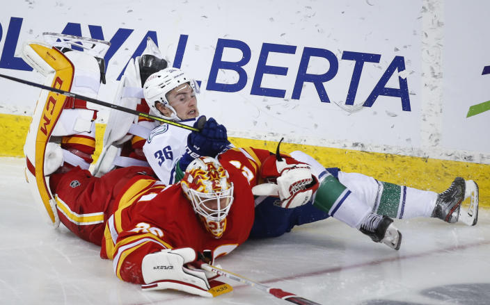 Vancouver Canucks' Nils Hoglander (36) is checked by Calgary Flames goalie Jacob Markstrom during the third period of an NHL hockey game Thursday, May 13, 2021, in Calgary, Alberta. (Jeff McIntosh/The Canadian Press via AP)