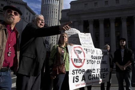 People hold signs protesting against the Stop-and-Frisk program, at a news conference outside the Federal Court in New York