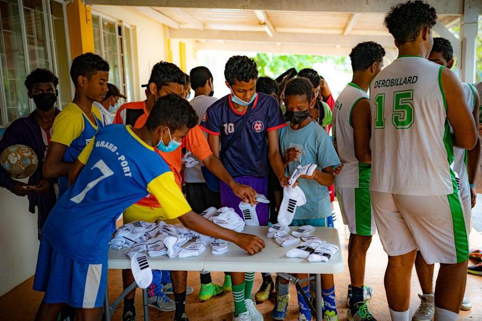 Young hopefuls collect new socks and other sporting equipment, donated by United Through Sport, in between coaching sessions at a training hub in Mauritius (Ben Birchall/PA) (PA Wire)