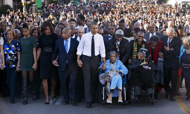 "<span class=""element-image__caption"">John Lewis holds hands with Barack and Michelle Obama as he and others who were beaten in 1965 walked across the Edmund Pettus Bridge in Selma in 2015 to mark the 50th anniversary of the march</span> <span class=""element-image__credit"">Photograph: Jacquelyn Martin/AP</span>"