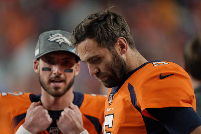 In this Thursday, Oct. 17, 2019 photo, Denver Broncos quarterback Joe Flacco (5) hangs his head as back-up quarterback Brandon Allen looks on during the second half of an NFL football game against the Kansas City Chiefs, in Denver. It took Allen four seasons and three different teams to get his shot at starting in the NFL. The fourth-year pro is taking over with Flacco sidelined by a herniated disk in his neck. (AP Photo/Jack Dempsey)