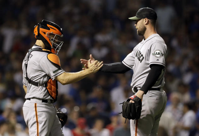 San Francisco Giants relief pitcher Hunter Strickland, right, celebrates with catcher Nick Hundley after they defeated the Chicago Cubs in a baseball game in Chicago, Saturday, May 26, 2018. (AP Photo/Nam Y. Huh)