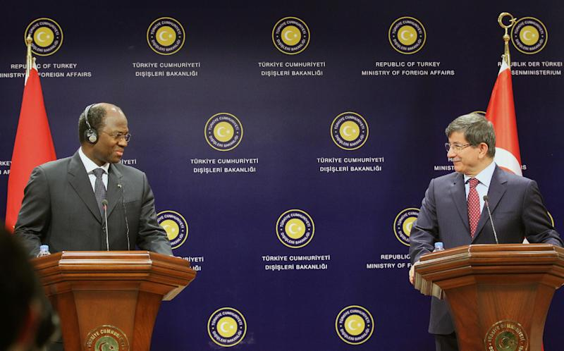 This photo made available by the Turkish Foreign Ministry shows the foreign minister of Burkino Faso, Djibril Yipene Bassole, left, and his Turkish counterpart Ahmet Davutoglu as they speak to the media shortly before Bassole briefly passed out during a live televised news conference in Ankara, Turkey, Thursday, May 9, 2013. Bassole leaned toward the lectern in front of him before knocking it over and collapsing on the raised platform. (AP Photo/Turkish Foreign Ministry, Cengiz Oguz Gumrukcu)