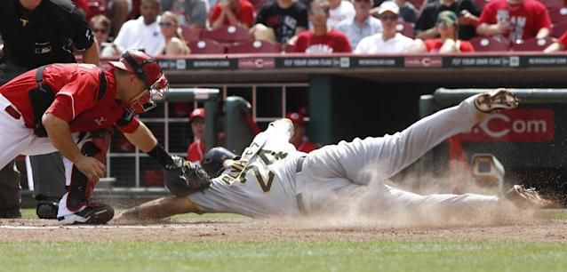 Pittsburgh Pirates' Pedro Alvarez (24) scores at home beating the tag from Cincinnati Reds catcher Devin Mesoraco, left, in the fifth inning of a baseball game, Sunday, July 13, 2014, in Cincinnati. (AP Photo/David Kohl)