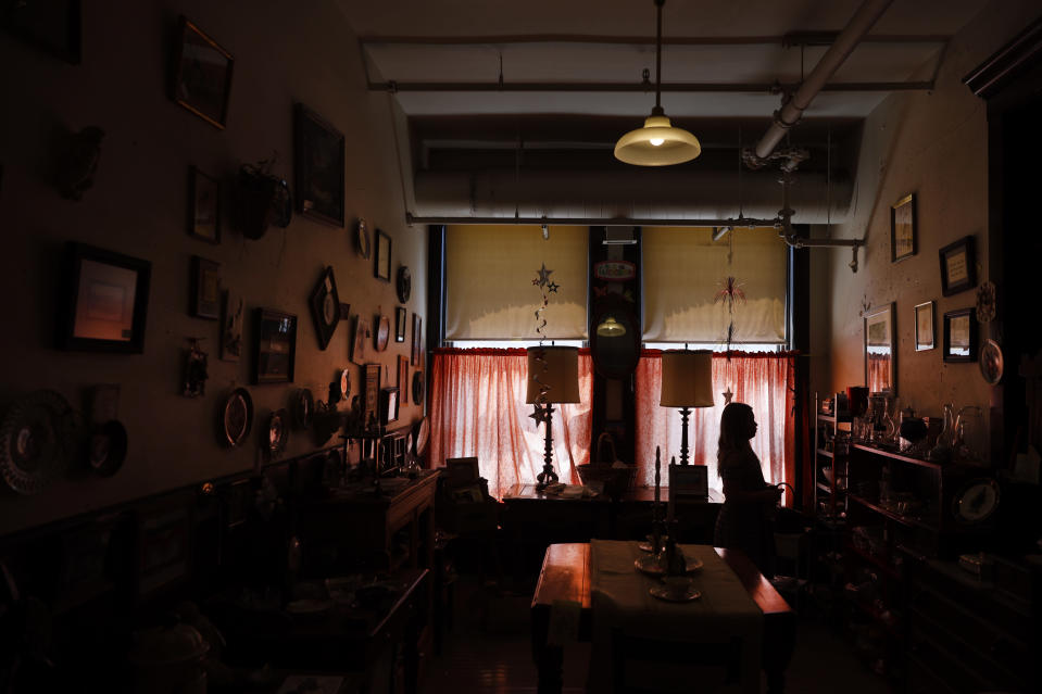 Cora Anderson, 9, from Macon, Ill., is silhouetted as she walks through the Galesburg Antiques Mall, Wednesday, June 16, 2021, in Galesburg, Il. (AP Photo/Shafkat Anowar)