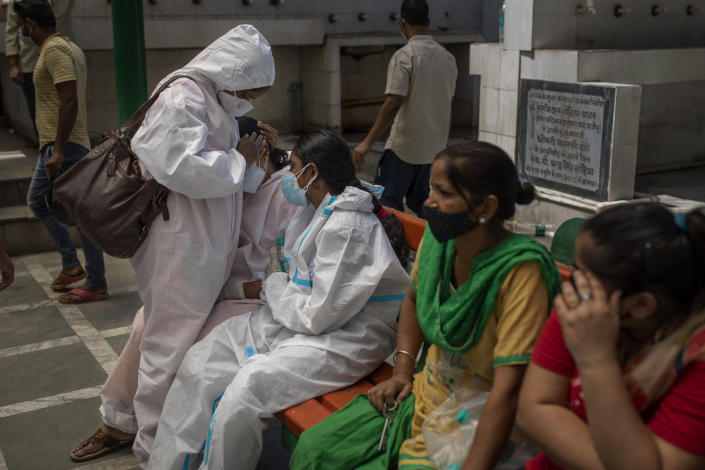 A woman is consoled by a relative at a crematorium during mass cremation of COVID-19 victims, in New Delhi, India, Saturday, April 24, 2021. Delhi has been cremating so many bodies of coronavirus victims that authorities are getting requests to start cutting down trees in city parks, as a second record surge has brought India's tattered healthcare system to its knees. (AP Photo/Altaf Qadri)