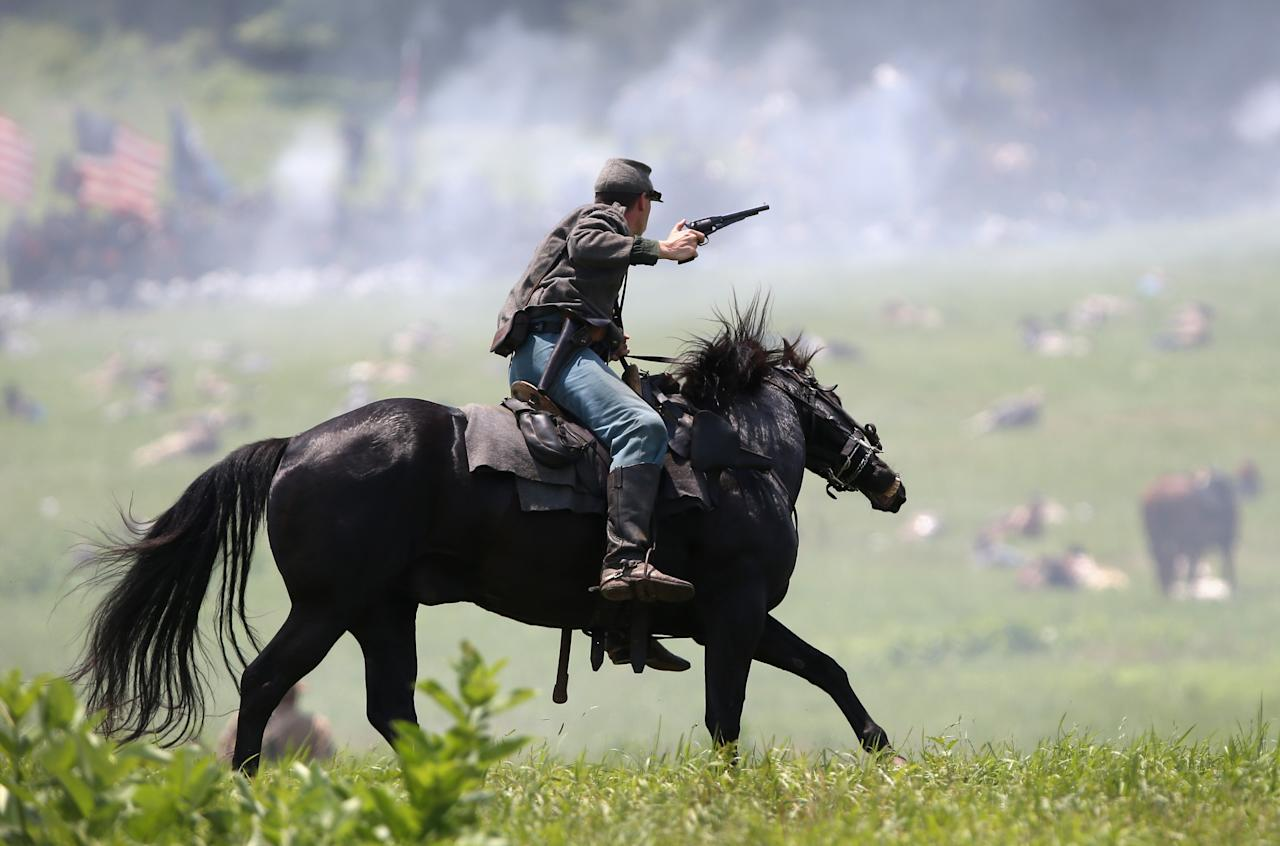 GETTYSBURG, PA - JUNE 30: A Confederate Civil War cavalry re-enactor shoots at Union soldiers during Pickett's Charge on the last day of a Battle of Gettysburg re-enactment on June 30, 2013 in Gettysburg, Pennsylvania. Some 8,000 re-enactors from the Blue Gray Alliance participated in the event, marking the 150th anniversary of the July 1-3, 1863 Battle of Gettysburg. Confederate General Robert E. Lee's Army of Northern Virginia was routed during the doomed frontal assault, considered the turning point in the Civil War and a watershed moment in U.S. history. Union and Confederate armies suffered a combined total of up to 51,000 casualties over three days, the highest number of any battle in the four-year war. Pickett's charge was named for the Confederate Maj. General George Pickett, whos division of rebel troops was annhilated in the attack. (Photo by John Moore/Getty Images)