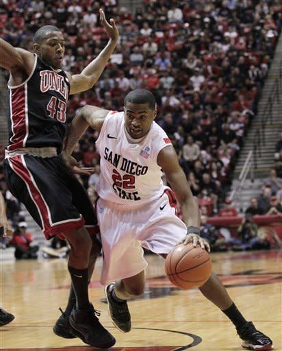 San Diego State's Chase Tapley, right, drives past UNLV's Mike Moser in the first half of an NCAA college basketball game, Saturday, Jan. 14, 2012, in San Diego. (AP Photo/Gregory Bull)