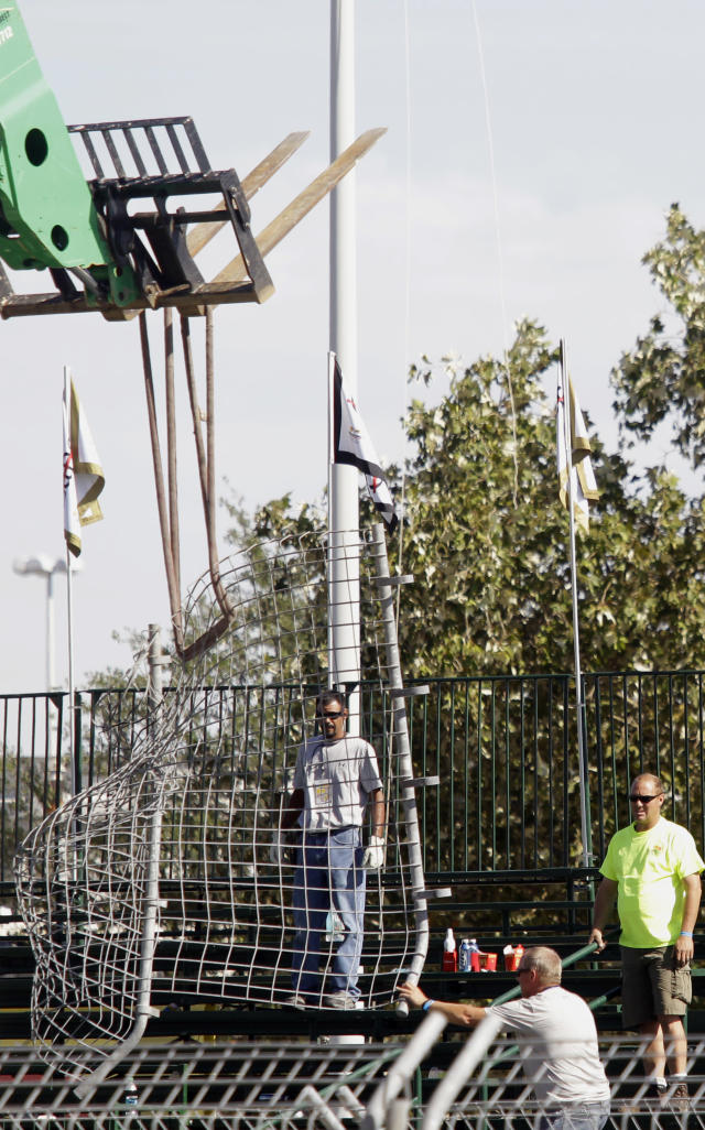 A piece of safety fencing is removed near a spectator grand stand after a crash during the second IndyCar Grand Prix of Houston auto race, Sunday, Oct. 6, 2013, in Houston. Driver Dario Franchitti, of Scotland, was taken to the hospital and several spectators were injured. (AP Photo/Patric Schneider)