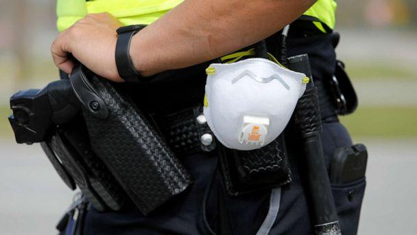 PHOTO: A North Charleston police officer carries a protective mask around his gun belt while working traffic at Roper St. Francis' North Charleston office, March 16, 2020, in North Charleston, S.C. (Mic Smith/AP, FILE)