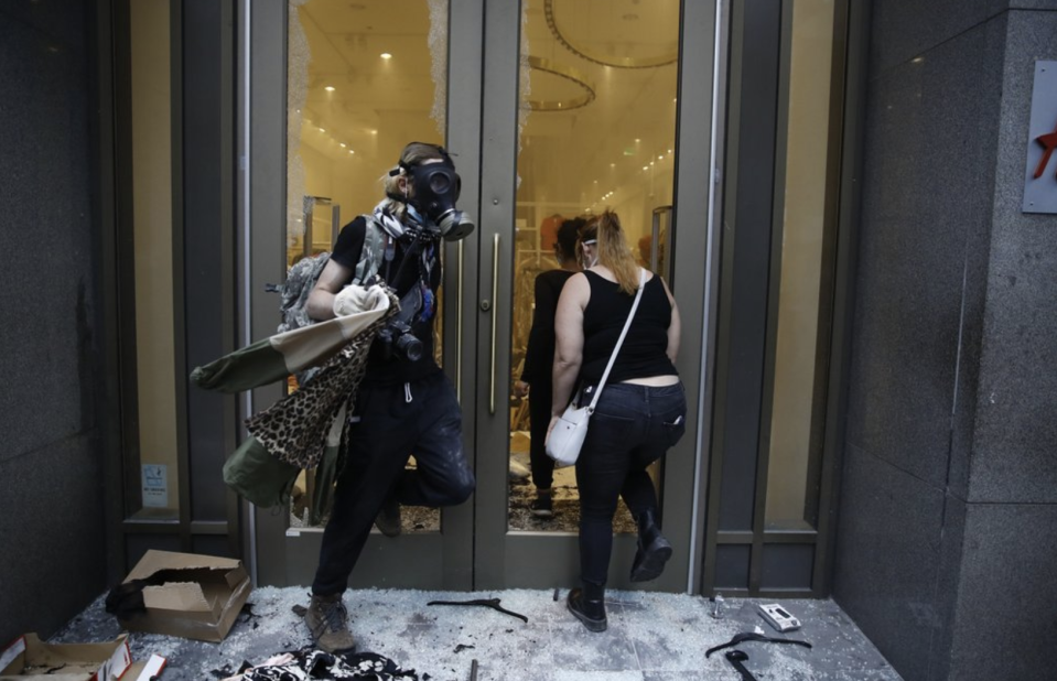 Pictured are two people at a smashed up H&M store in Philadelphia - one is wearing a mask.