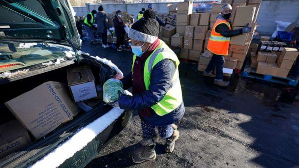 PHOTO: Volunteers wear masks as they load food in to cars at the Utah Food Bank's mobile food pantry, Nov. 12, 2020, in West Valley City, Utah. (Rick Bowmer/AP)