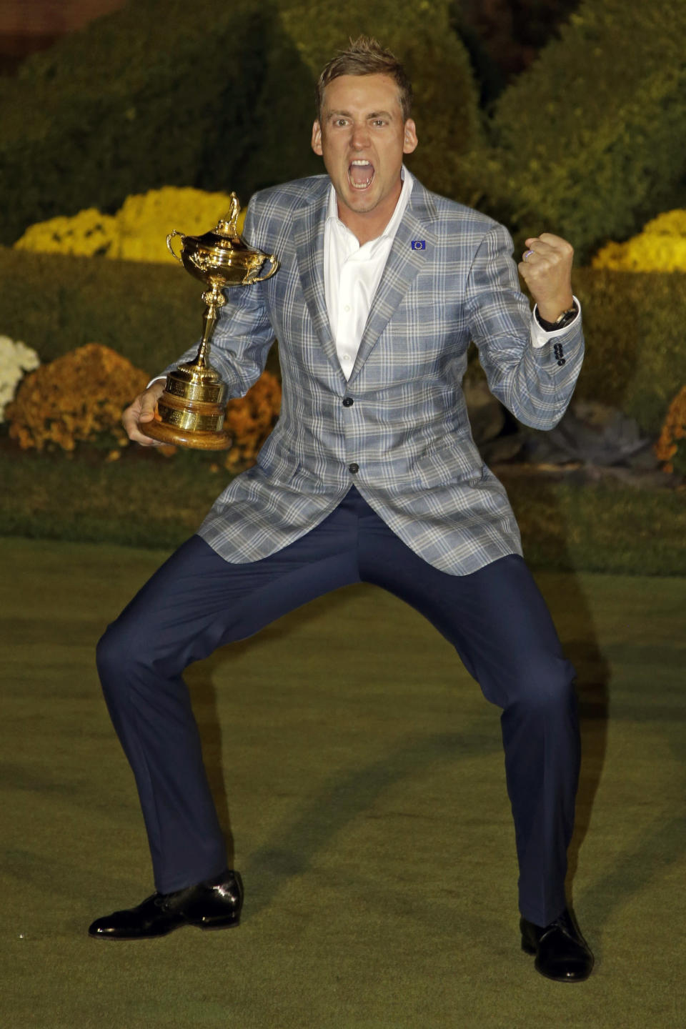 FILE - Europe's Ian Poulter celebrates with the trophy after winning the Ryder Cup PGA golf tournament at the Medinah Country Club in Medinah, Ill., in this Sept. 30, 2012, file photo. Poulter is 14-6-2 in his previous six Ryder Cups. He is 5-0-1 in singles. He has been on five winning teams and only one loser. (AP Photo/Chris Carlson, File)