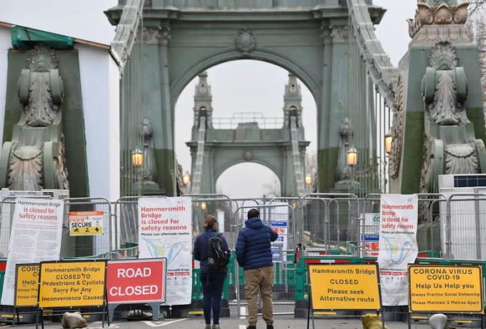 Pedestrians view Hammersmith Bridge, the closure of which has caused the annual Oxford versus Cambridge boat race on the River Thames to be relocated, London, Britain