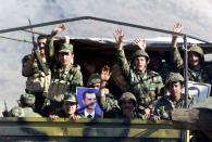 FILE PHOTO: Syrian army troops wave from truck driving towards the Lebanese Syrian border in the Bekaa valley.