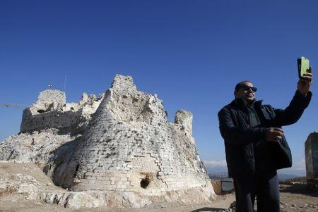 A man takes a selfie in front of the newly restored Crusader Beaufort castle in Arnoun village, south Lebanon January 18, 2015. REUTERS/Ali Hashisho/Files