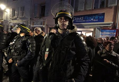 French riot policemen stand guard in front of the campaign headquarters of David Rachline, France's far-right National Front political party member head of the list for municipal elections, in Frejus